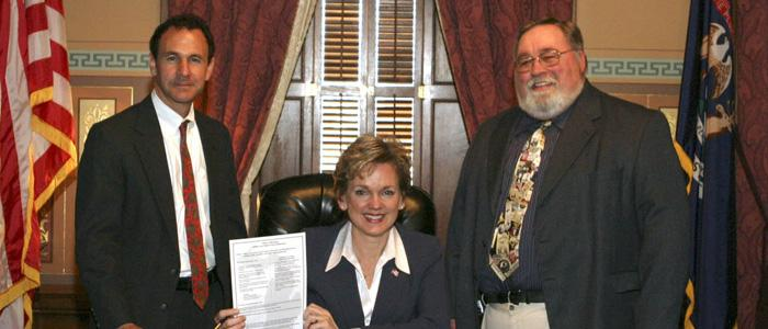 Governor Jennifer Granholm signs worker safety legislation with John DeTizio and Dale Threehouse witnessing.